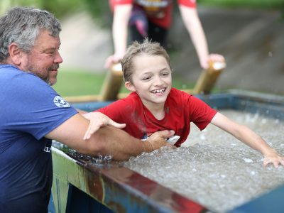 Man helping Kid in Ice Bath Obstacle - ASCO Spartacus Dash